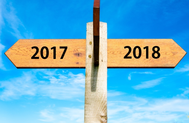 Wooden signpost with two opposite arrows over clear blue sky, year 2017 and 2018 signs, Happy New Year conceptual image